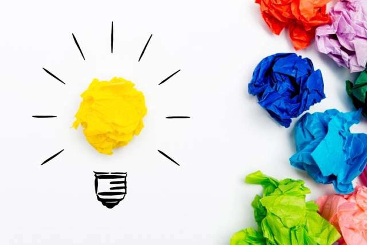 criatividade-e-inovacao - papel amassado amarelo dando corpo a um desenho de lâmpada