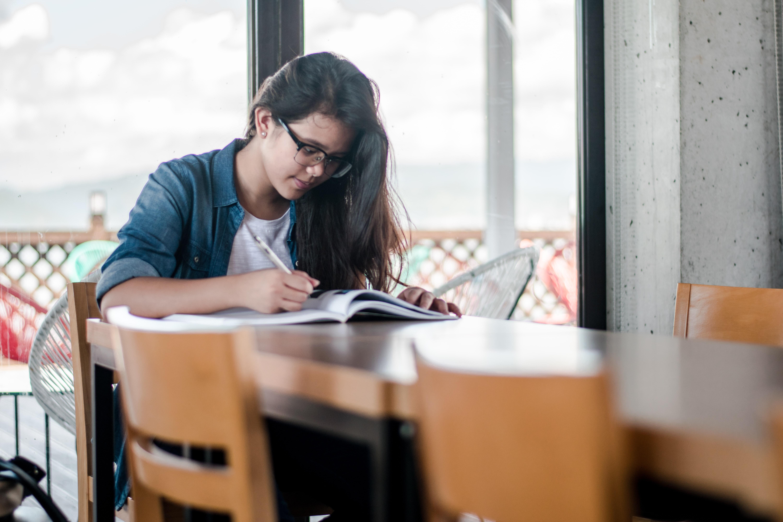 cronograma-de-estudos-ead - menina com o caderno apoiado em uma mesa escrevendo