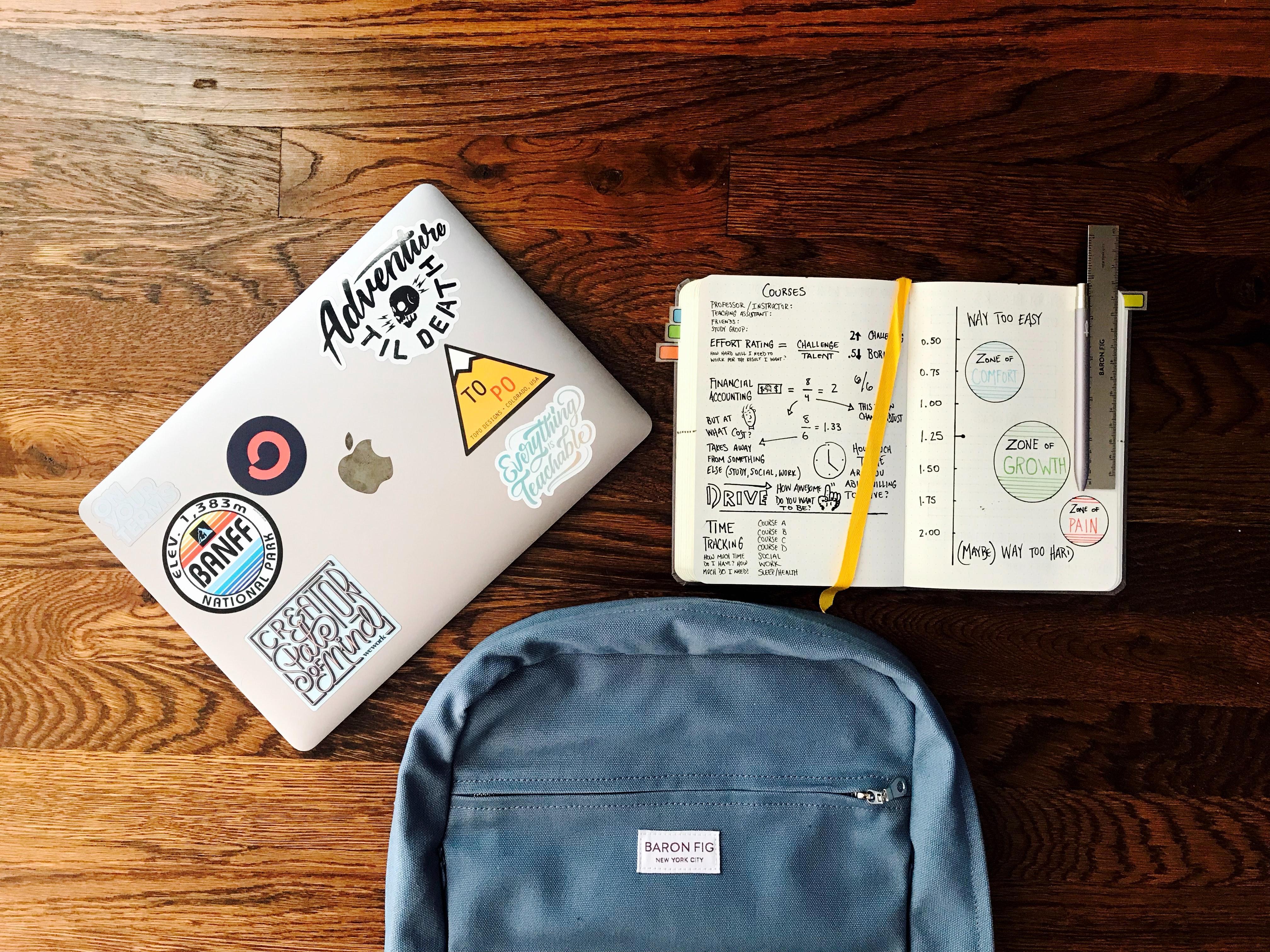 cronograma-de-estudos - mesa com notebook, caderno aberto e mochila em cima