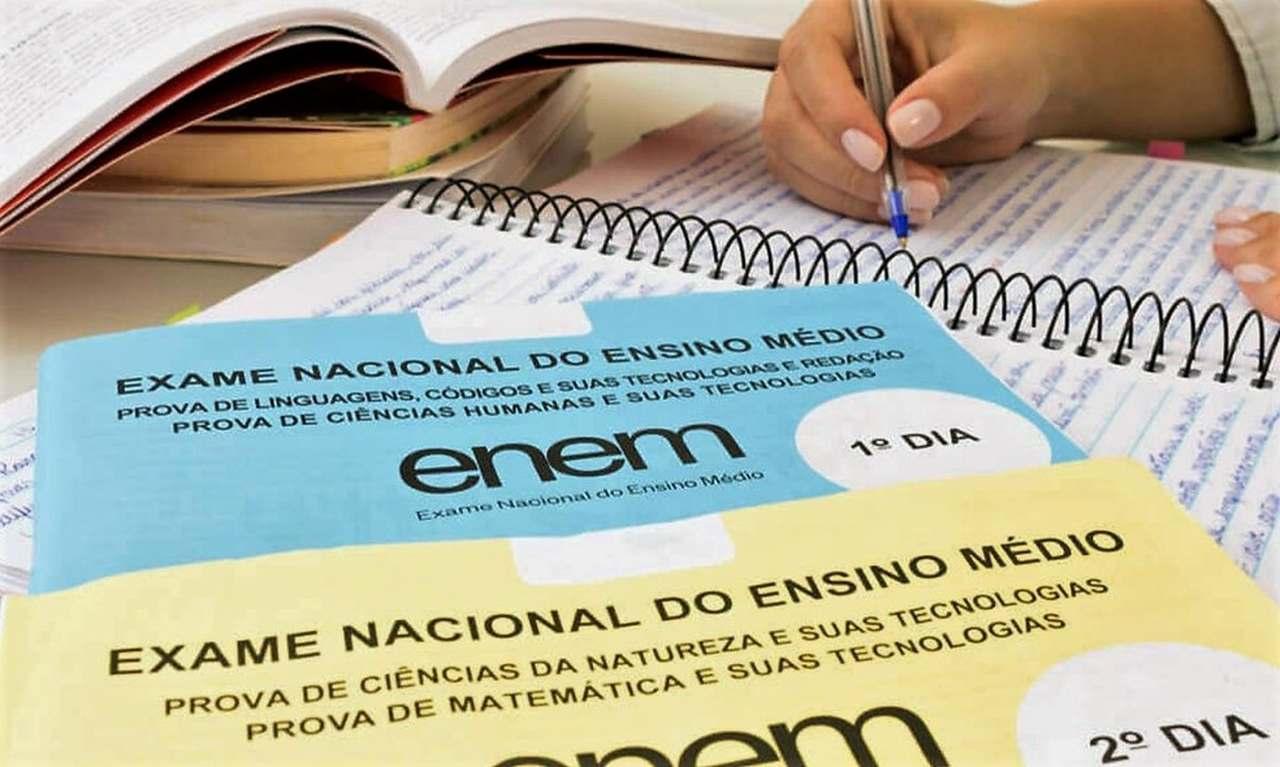 enem-2021 - pessoa escrevendo próximo a cadernos do enem