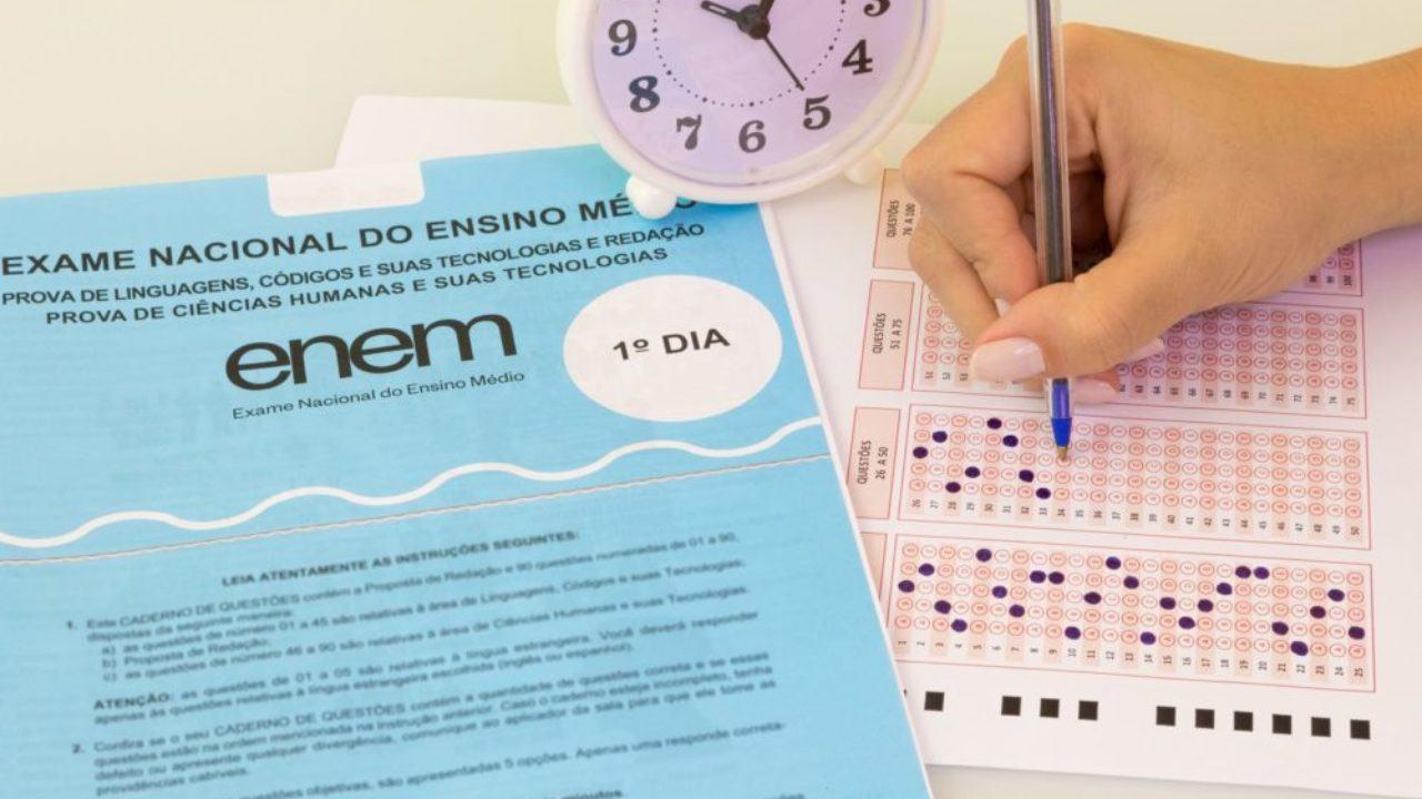 materias-que-caem-no-enem-2021 - pessoa escrevendo, relógio e caderno azul do enem
