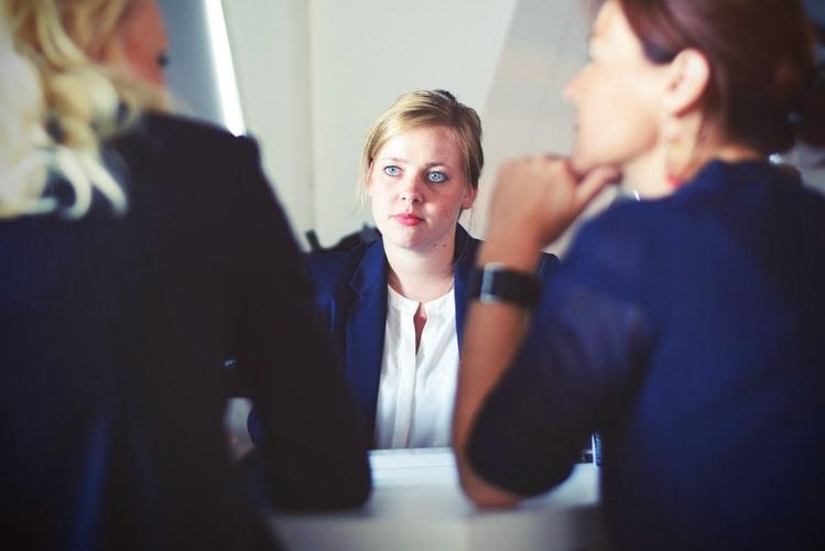 Moça sentada de frente para uma mesa sendo entrevistada por outras duas mulheres.