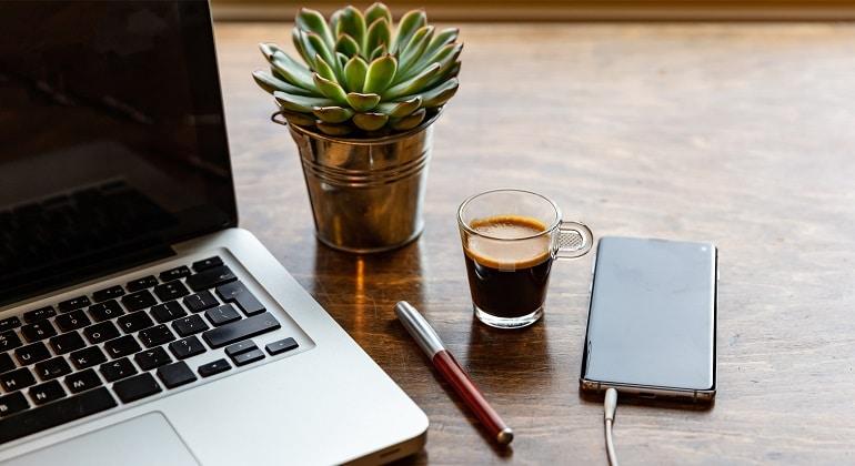 o-que-precisa-para-trabalhar-homo-office - mesa de trabalho com notebook, xícara de café e celular carregando