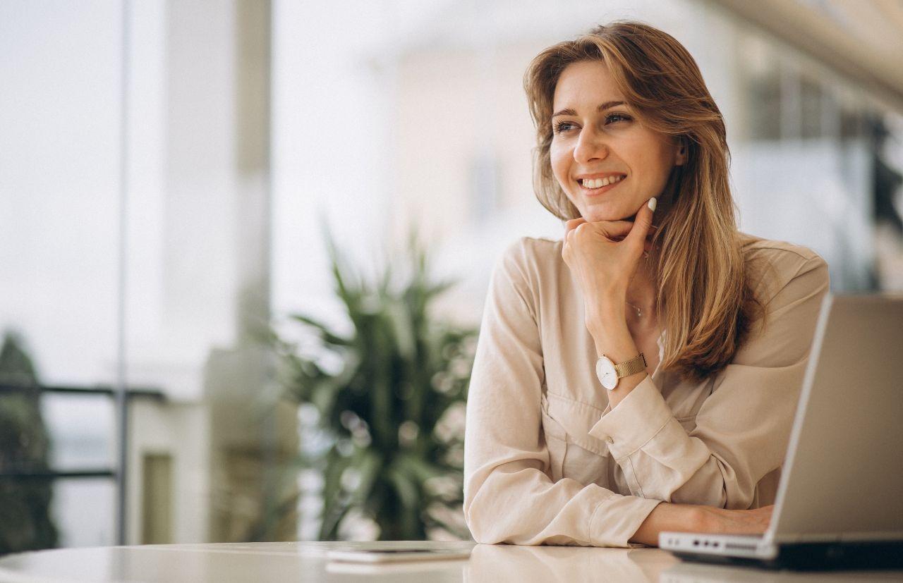 qualidades-profissionais - mulher com cabeça apoiada no queixo e sorridente