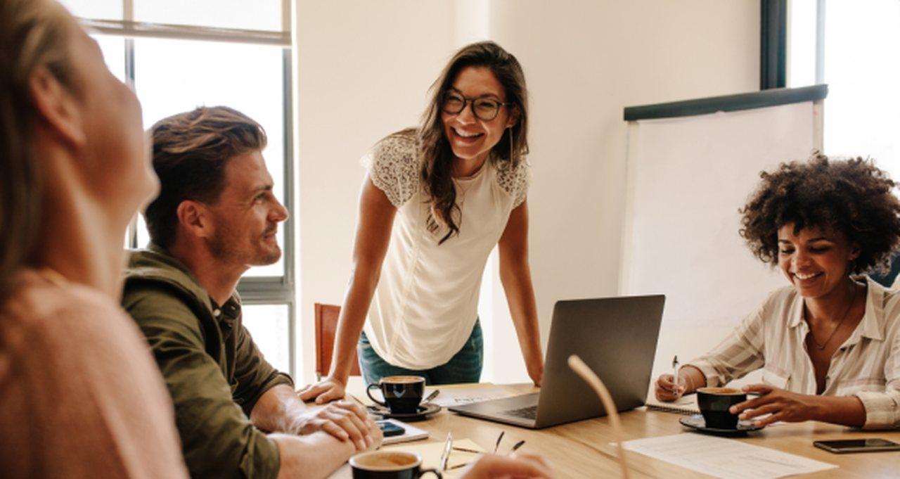 qualidades-profissionais - mulher sorridente cercada por colegas de trabalho