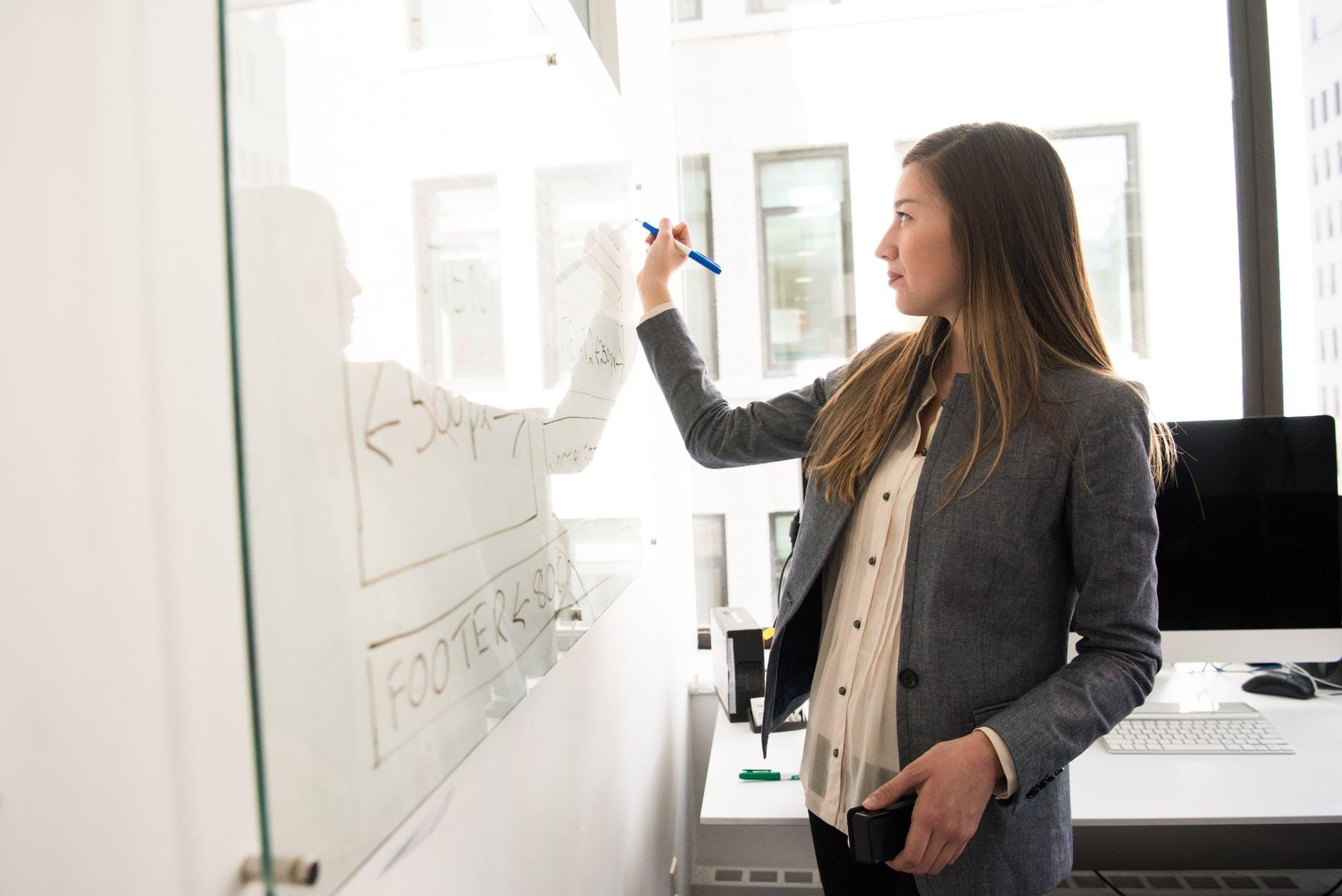 mulher jovem escrevendo em quadro branco.