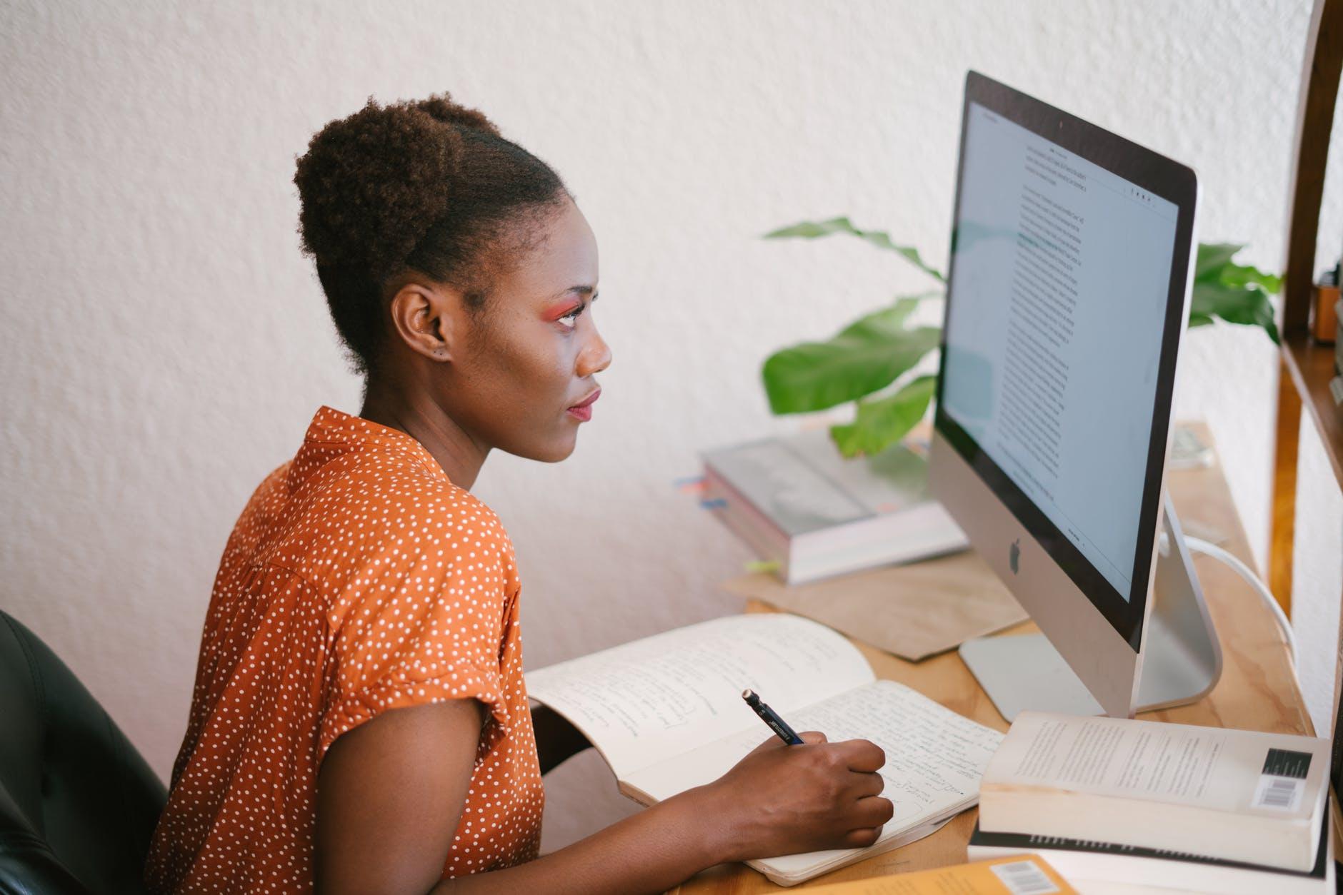 mulher jovem observando computador enquanto faz anotações