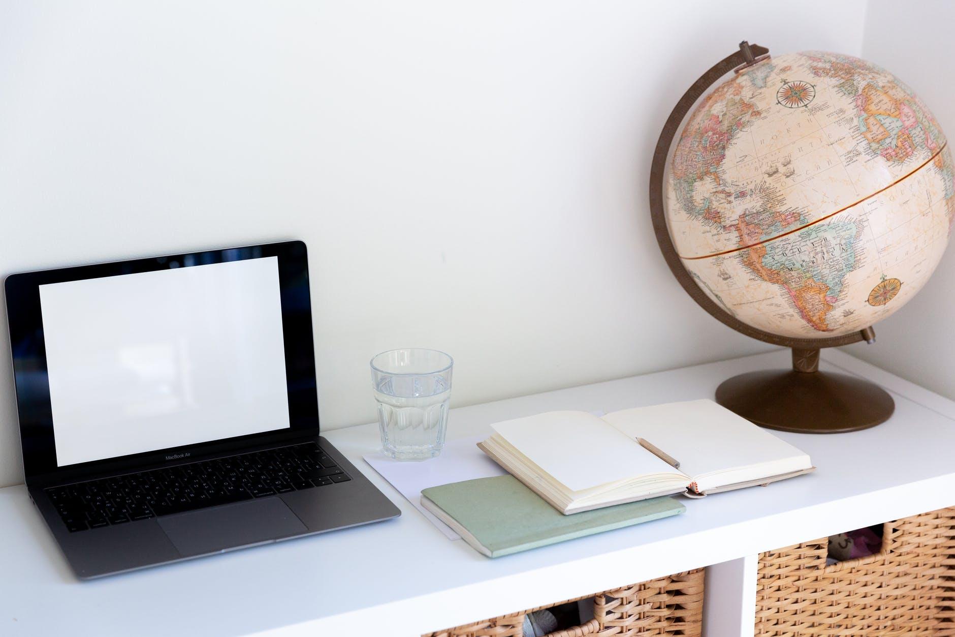 mesa de estudos com notebook e livros.