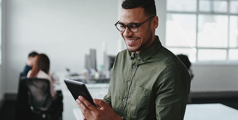 Aluno da graduação EAD sorrindo, usando um tablet.