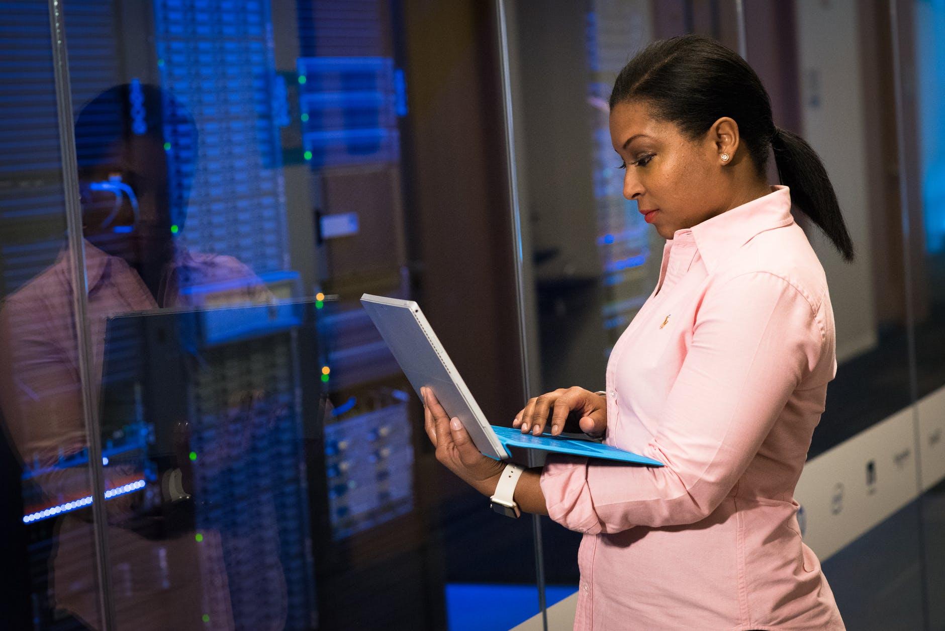 mulher jovem com um notebook em mãos. Ao fundo, ambiente industrial.