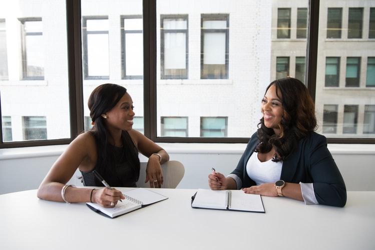 duas mulheres sorrindo enquanto fazem anotações em cadernos.