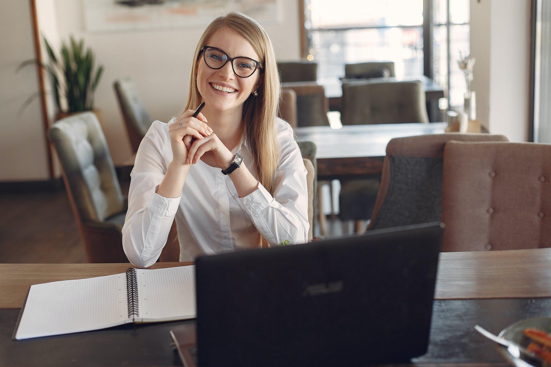 menina sorrindo em frente a um notebook.